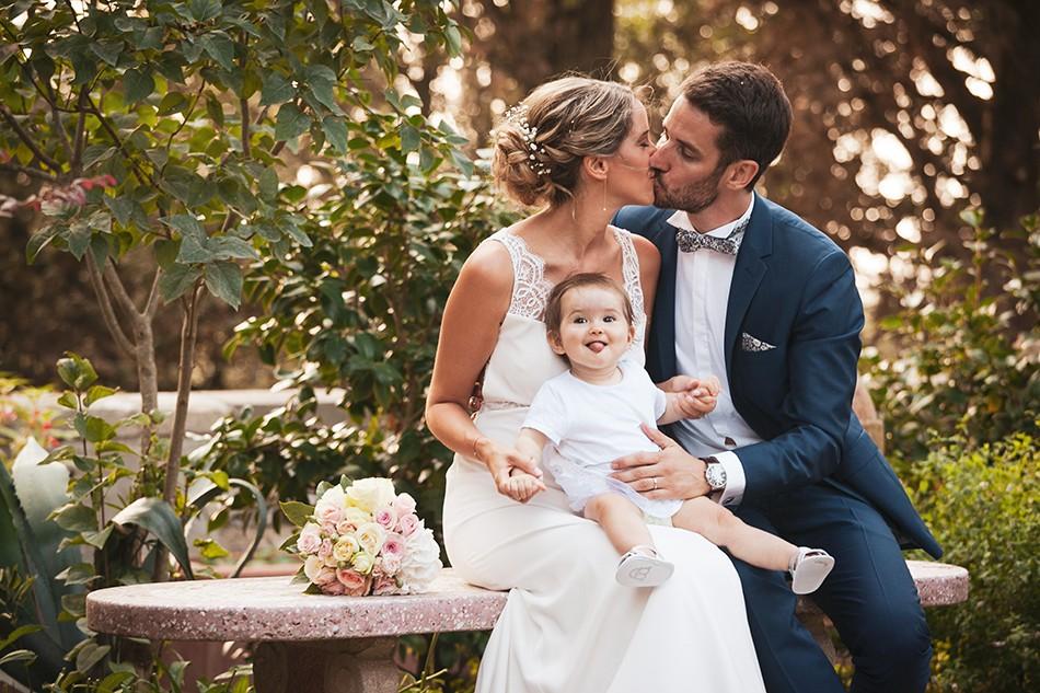 gli sposi si baciano sulla panchina con la figlia in braccio