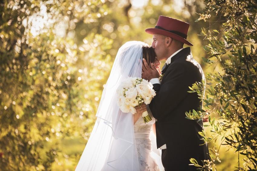 gli sposi si baciano nel giardino di villa scorzi