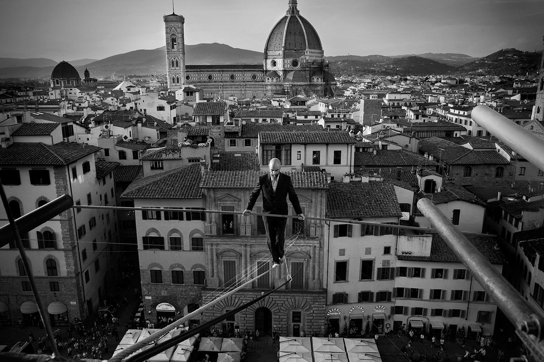 funambolo andrea loreni che attraversa piazza della signoria a Firenze