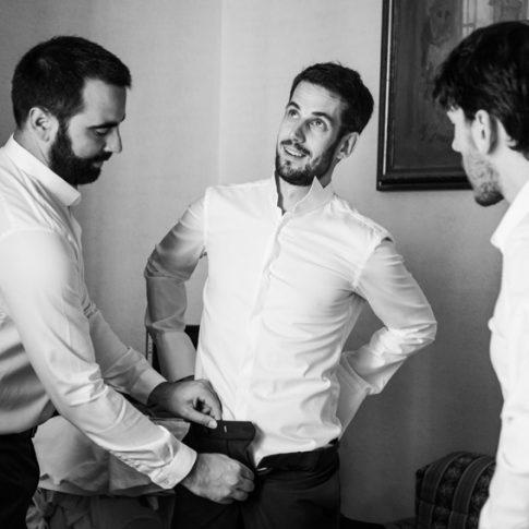 gli amici aiutano lo sposo ad allacciare i pantaloni durante i preparativi a Villa il Poggione