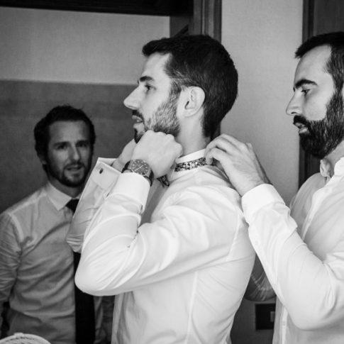 gli amici aiutano lo sposo a vestirsi durante i preparativi