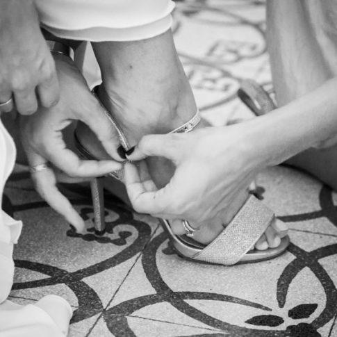 le amiche allacciano le scarpe alla sposa