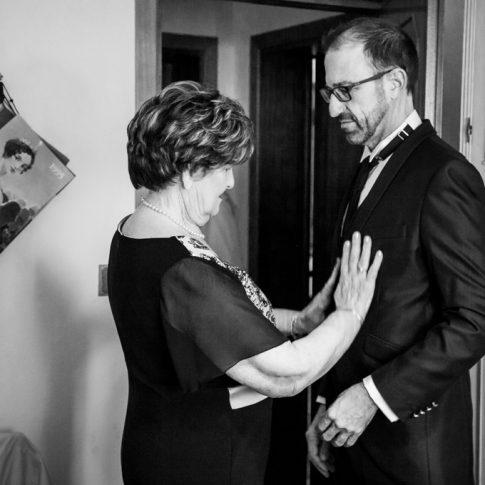 la madre aiuta lo sposo a vestirsi