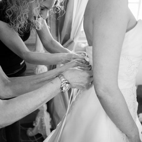 la madre e un'amica allacciano il vestito alla sposa, abito da sposa