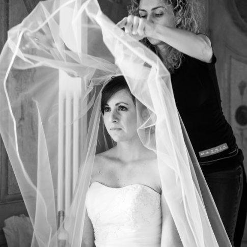 la parrucchiera mette il velo alla sposa durante i preparativi