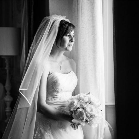 la sposa guarda fuori dalla finestra prima di scendere le scale