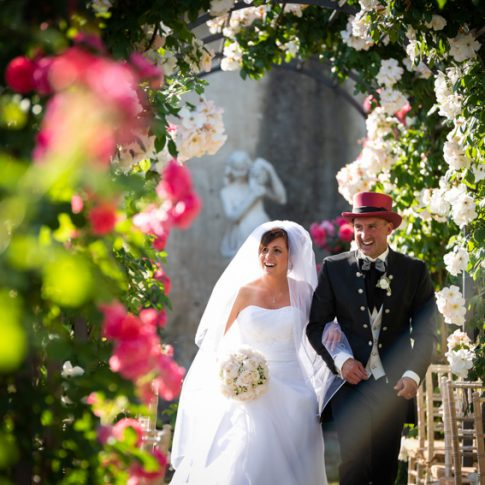 gli sposi camminano per mano mentre escono dal roseto di villa scorzi alla fine della cerimonia