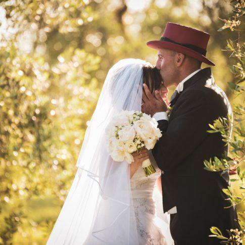 lo sposo bacia in fronte la sposa alla luce del tramonto a villa scorzi