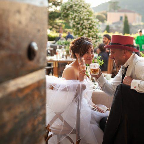 gli sposi brindano durante la cena all'aperto nel cortile di villa scorzi