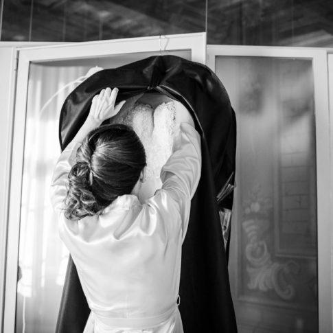 la sposa prende l'abito appeso alla porta a villa poschi