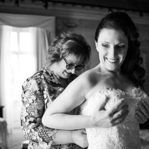 la madre allaccia il vestito alla sposa