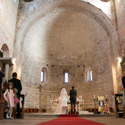 sposi presi da dietro nella navata centrale della basilica di san piero a grado