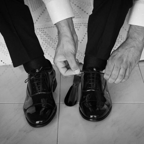 sposo che si allaccia le scarpe da matrimonio