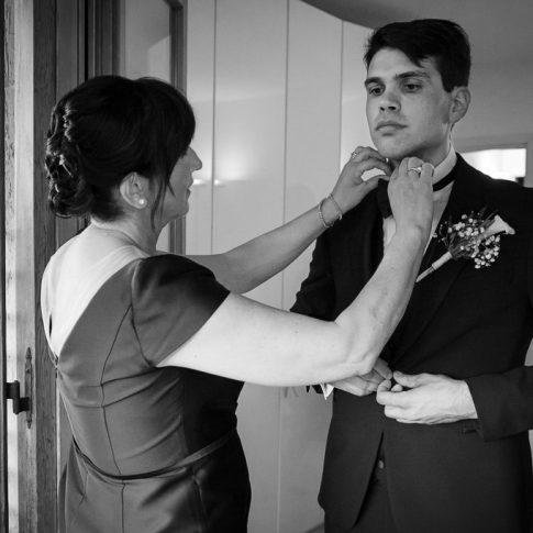 madre aiuta lo sposo a vestirsi