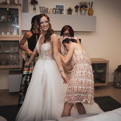 le amiche allacciano l'abito da sposa
