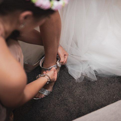 un'amica allaccia la scarpa alla sposa
