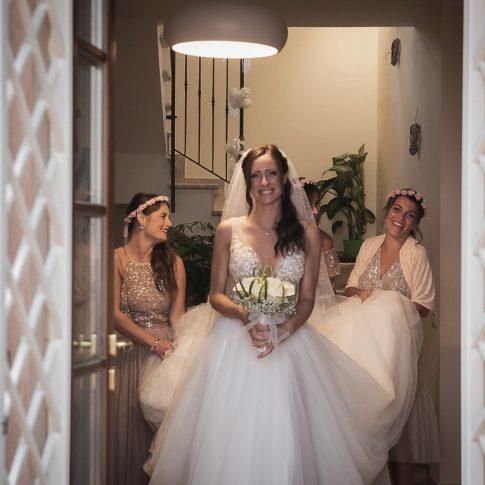 la sposa esce di casa accompagnata dalle amiche