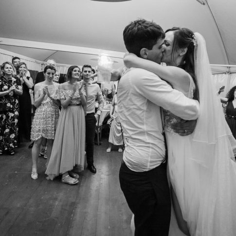 foto bianco e nero degli sposi che si baciano e amici che applaudono