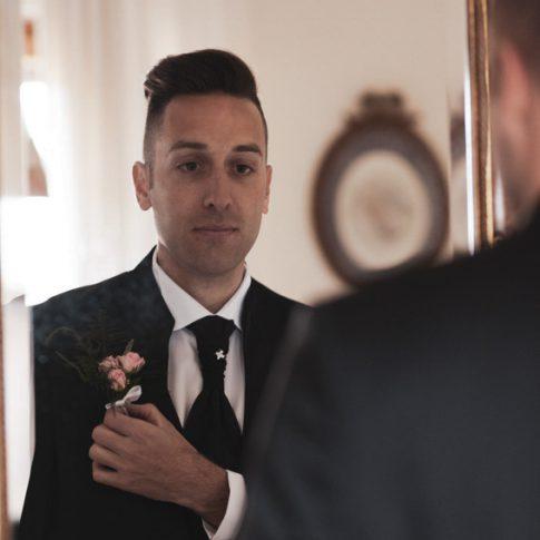 sposo si guarda allo specchio vestito per il matrimonio