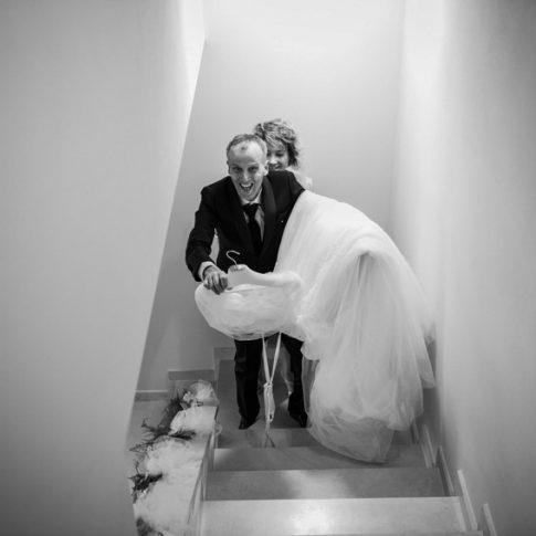 padre della sposa sale le scale col vestito