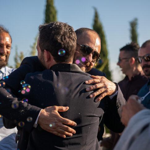 lo sposo abbraccia un amico tra le bolle di sapone alla fine della cerimonia