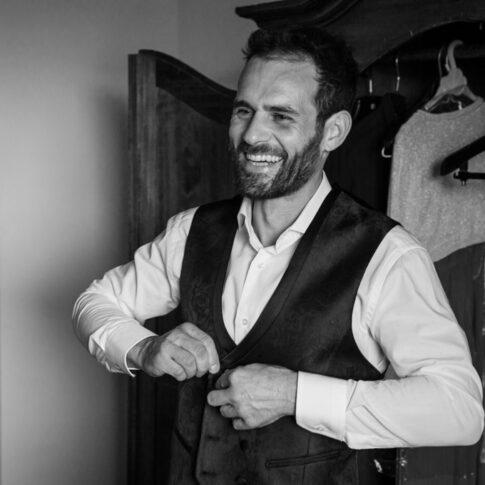 lo sposo sorridente abbottona il gilet del vestito durante i suoi preparativi all'agriturismo di Colleoli