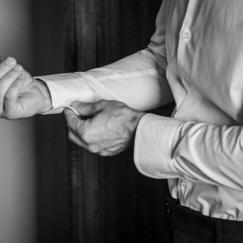 lo sposo abbottona i polsini della camicia durante la vestizione