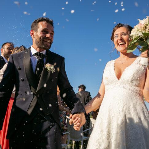 gli sposi felici e sorridenti si tengono per mano durante il lancio del riso alla fine della cerimonia civile all'agriturismo di Colleoli