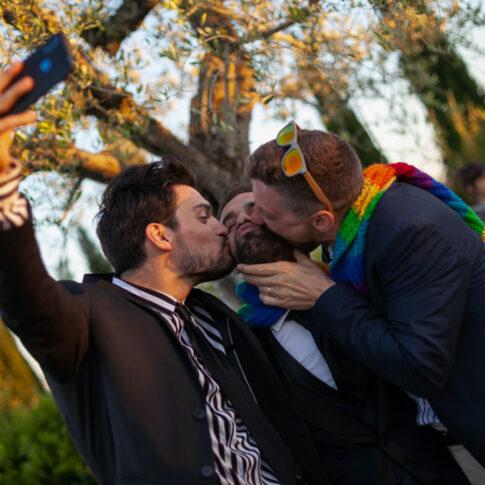due amici baciano lo sposo mentre si fanno un selfie