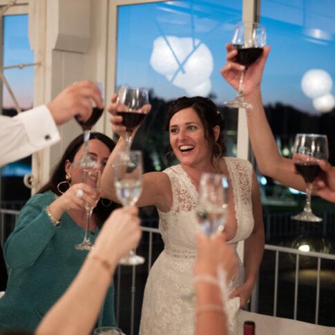 la sposa alza il calice per un brindisi al tavolo con amici