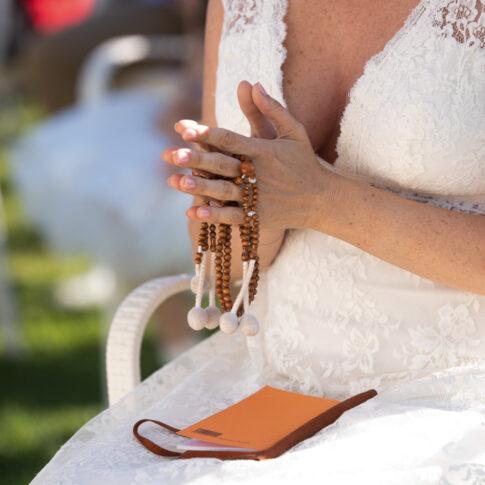 la sposa con le mani giunte durante la preghiera della cerimonia buddista