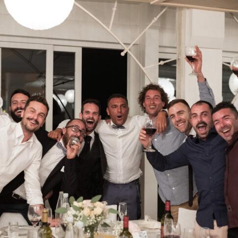 lo sposo e i suoi amici si abbracciano ed esultano durante la cena