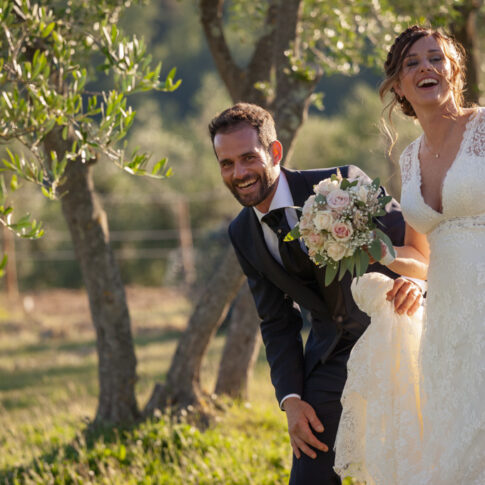 sposi felici e sorridenti alla fattoria dell'agriturismo di Colleoli con la luce del tramonto