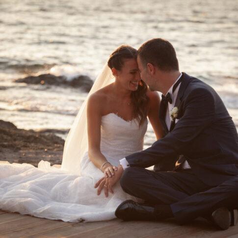 foto di un momento di intimità tra gli sposi davanti al mare alla luce del tramonto
