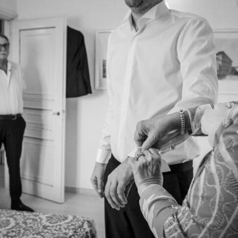 la madre abbottona i gemelli della camicia allo sposo