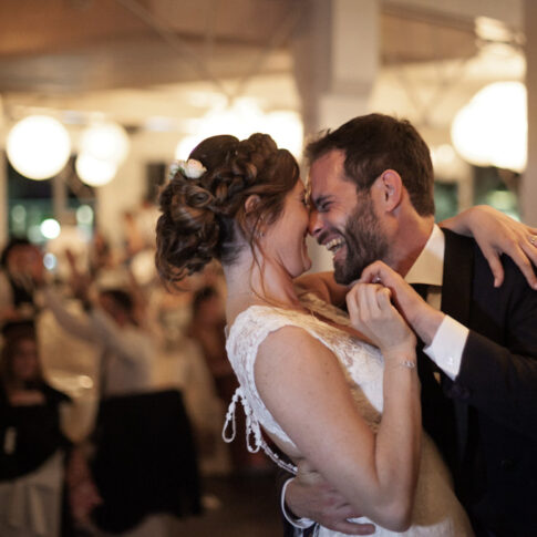 gli sposi ridono e si abbracciano durante il ballo alla cena di matrimonio