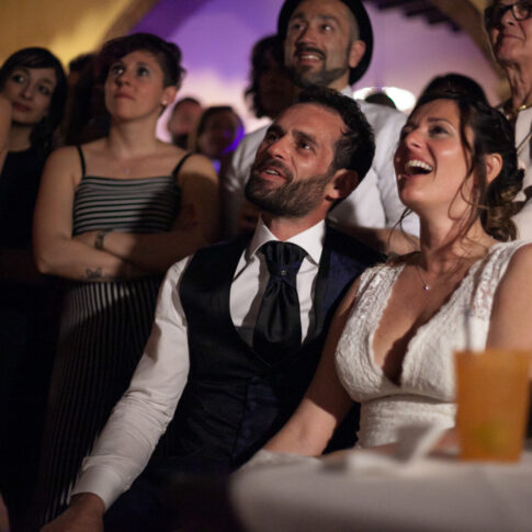 gli sposi emozionati guardano con gli amici un video ricordo dei loro momenti più felici
