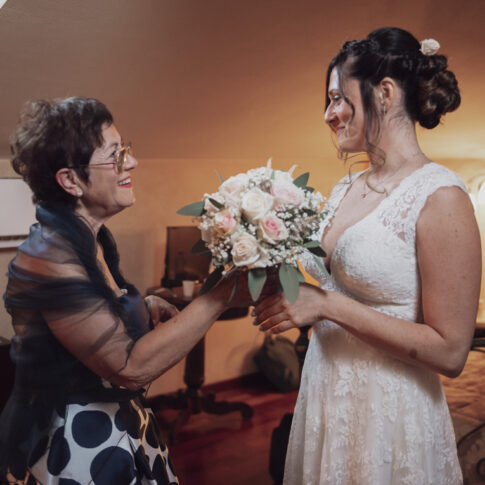 la madre dello sposo consegna il mazzolino alla sposa in camera all'agriturismo di Colleoli