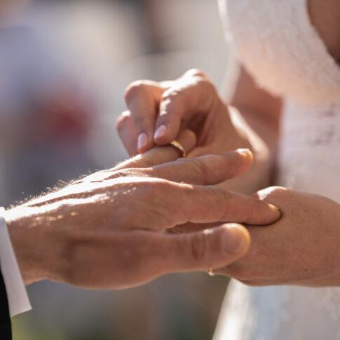 dettaglio della sposa che mette l'anello al dito dello sposo