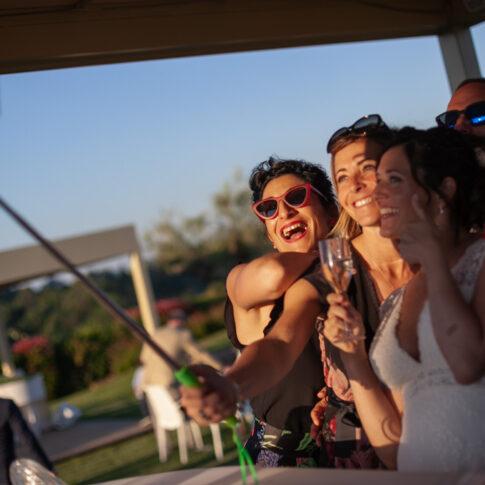 la sposa e le amiche si fanno un selfie alla luce del tramonto