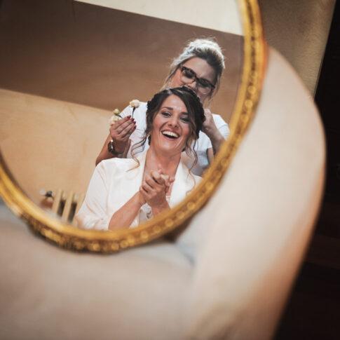 riflesso nello specchio appoggiato sul divano della sposa felice e sorridente durante l'acconciatura