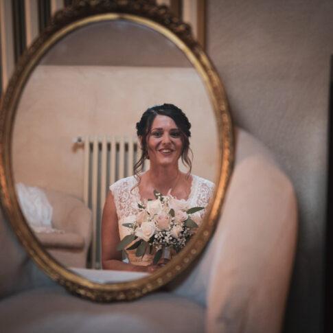 riflesso nello specchio della sposa sorridente col mazzolino in mano, in attesa di scendere per la cerimonia all'agriturismo di Colleoli