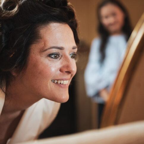 la sposa sorridente si guarda allo specchio durante il trucco