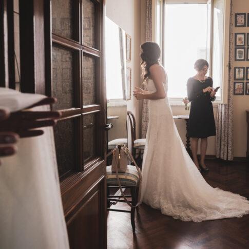 la sposa si guarda allo specchio mentre l'amica attende con il velo in mano