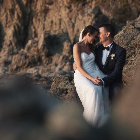 momento di intimità tra gli sposi che si guardano su uno scoglio alla luce del tramonto
