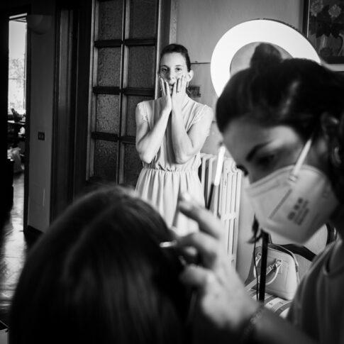 l'amica guarda emozionata la sposa durante il trucco