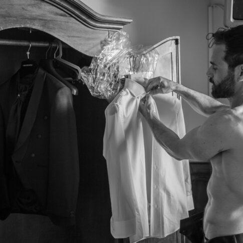 lo sposo a torso nudo prepara la camicia del vestito per indossarla